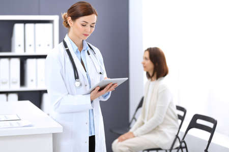 Happy doctor woman at work. Portrait of female physician using tablet computer while standing near reception desk at clinic or emergency hospital. Patient woman sitting at the background. Medicine concept