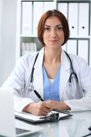 Doctor woman at work. Physician filling up medical history records form at the desk. Medicine, healthcare  concept