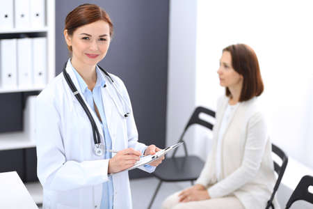 Doctor woman at work. Portrait of female physician filling up medical form while standing near reception desk at clinic or emergency hospital. Patient woman sitting at the background. Medicine concept Stockfoto