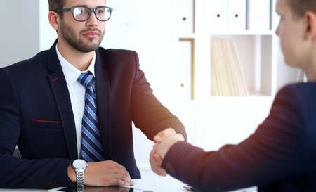 Business handshake at meeting or negotiation in the office. Two businessmen partners are satisfied because signing contract or financial papers Stockfoto