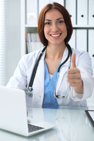 Close up of female doctor thumbs up. Happy cheerful smiling brunette physician ready to examine patient. Medicine, healthcare and help concept