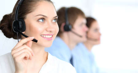 Call center operators at work. Focus at  business woman in headset Stockfoto