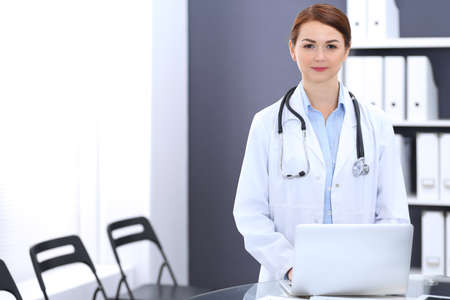 Happy doctor woman at work. Portrait of female physician using laptop computer while standing near reception desk at clinic or emergency hospital. Medicine concept