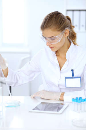 Female scientific researcher or blood test assistant at work in laboratory. Science, medicine and pharmacy concept