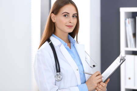 Doctor woman filling up medical form while standing near window in hospital office. Happy physician at work. Medicine and health care concept Stockfoto