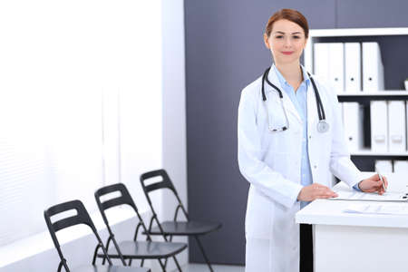 Doctor woman at work. Portrait of female physician filling up medical form while standing near reception desk at clinic or emergency hospital. Medicine concept
