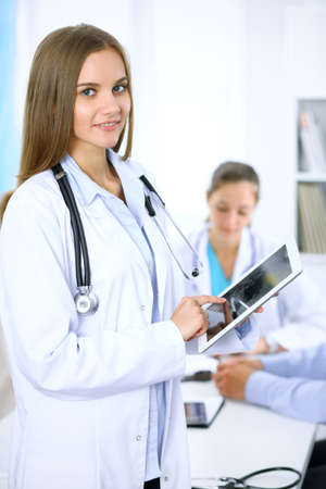 Doctor using tablet computer, close-up of hands at touch pad screen. Patient is at the background