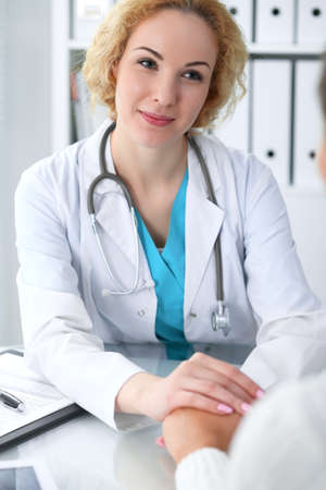 Doctor woman looking at  patient while speaking to her and reassuring. Medicine, healthcare and help concept Stockfoto