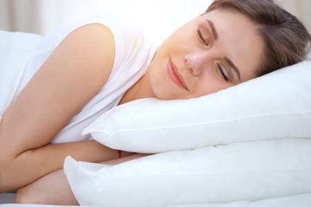 Beautiful young and happy woman sleeping while lying in bed comfortably and blissfully smiling Stockfoto