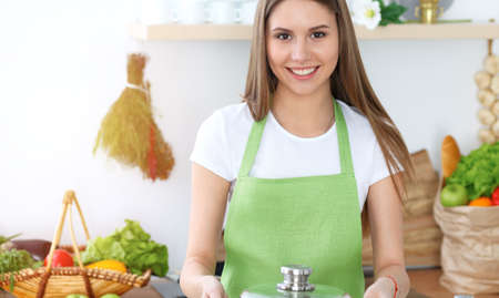 Young happy woman cooking soup in the kitchen. Healthy meal, lifestyle and culinary concept. Smiling student girl preparing vegetarian meal at home