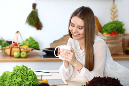 Young happy woman holding white cup and looking at the camera while sitting at wooden table in the kitchen among green vegetables. Good morning, lifestyle or cooking concept Stockfoto