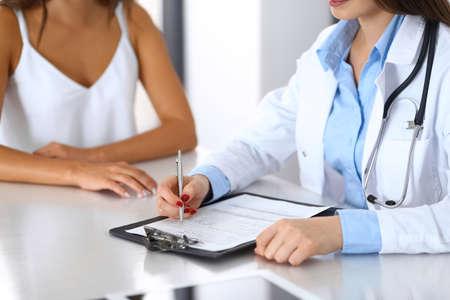 Médico y paciente feliz hablando mientras está sentado en el escritorio, primer plano de las manos. El médico o terapeuta que completa los registros del historial médico. Concepto de atención médica, medicina y servicio al paciente.