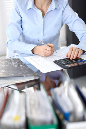 Bookkeeper woman or financial inspector making report, calculating or checking balance, close-up. Business portrait. Copy space area for audit or tax concepts