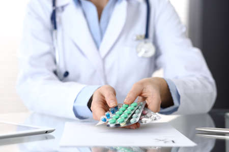 Doctor holding pack of different tablet blisters closeup. Life save service, legal drug store, prescribe medication, blood pressure, disease healing concept