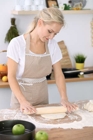 Little girl and her blonde mom in beige aprons  playing and laughing while kneading the dough in kitchen. Homemade pastry for bread, pizza or bake cookies. Family fun and cooking concept Stock Photo