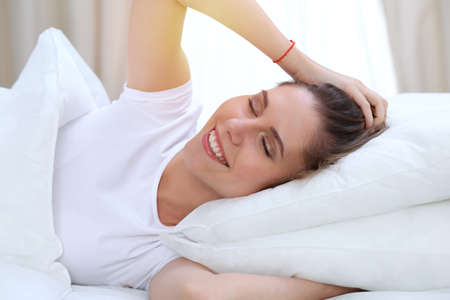 Bella donna giovane e felice che allunga le mani mentre giace a letto comodamente e sorride beatamente prima di svegliarsi al mattino. Concetto di sonno