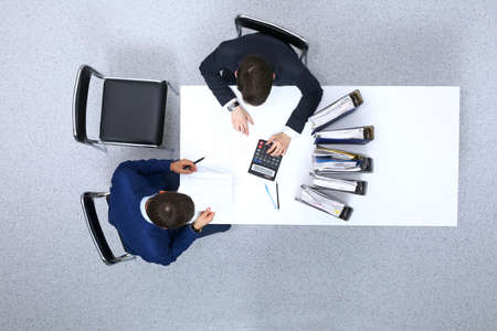Two businessmen sitting at the table, view from above. Bookkeeper or financial inspector  making report, calculating or checking balance