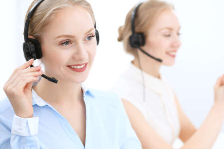 Bright and sunny call center. Group of blonde women in headset at work. Office and business concept