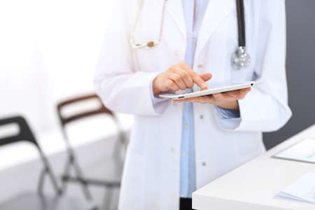 Female physician using digital tablet  while standing near reception desk at clinic or emergency hospital. Unknown doctor woman at work. Medicine concept 版權商用圖片