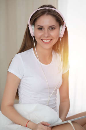 Woman listening music in bed with pink headphones after wake up, entering a day happy and relaxed after good night sleep