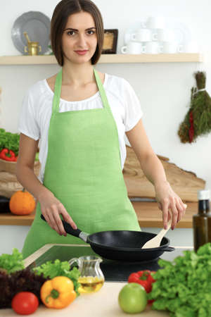 Beautiful Hispanic woman cooking in kitchen. Girl frying in a skillet something. Healthy meal and householding concepts