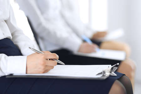 Business people taking part at conference or training at office, close-up. Women sitting on chairs and making notes like at queue or meeting Stok Fotoğraf