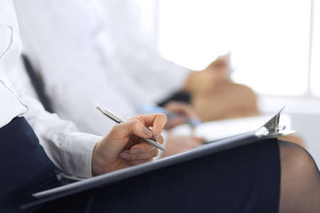 Business people taking part at conference or training at office, close-up. Women sitting on chairs and making notes like at queue or meeting Imagens