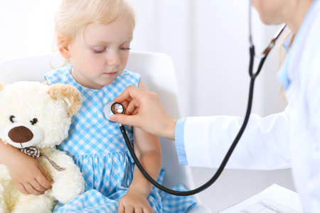 Doctor and a little blonde girl. Usual health exam. Medicine and healthcare concept Imagens
