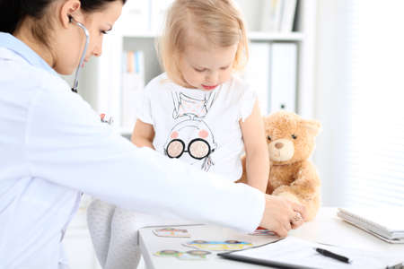 Doctor and patient baby in hospital. Little girl is being examined by pediatrician with stethoscope. Health care, insurance and help concept Imagens