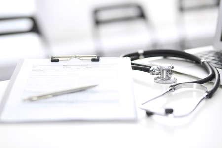 Estetoscopio, portapapeles con formulario médico en el mostrador de recepción del hospital con ordenador portátil. Herramientas médicas en la mesa de trabajo del médico.Concepto de atención médica y medicina
