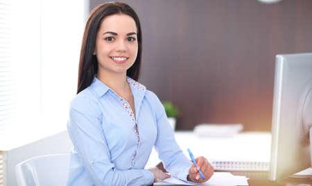 Mujer de negocios morena joven parece una chica estudiante que trabaja en la oficina. Niña hispana o latinoamericana feliz en el trabajo y demasiado ocupada