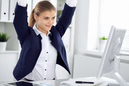 Modern business woman or confident female accountant in office with arms raised represents success at work. Student girl during exam preparing. Audit, tax service or education concept Banco de Imagens