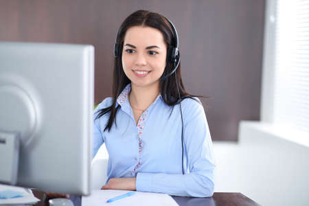 Young brunette business woman looks like a student girl working in office. Hispanic or latin american girl talking by headphones at pc 版權商用圖片