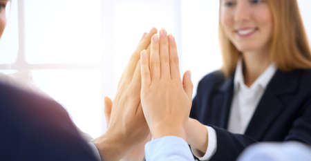 Business people happy showing teamwork and giving five showing unity and partnership. Success and friendship concepts