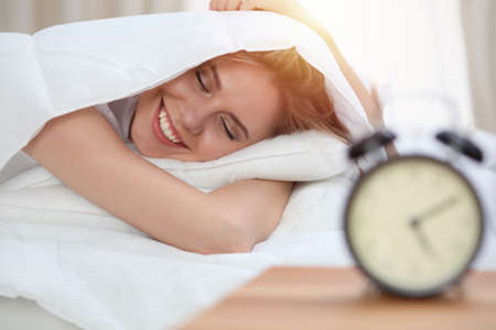 Beautiful young and happy woman sleeping while lying in bed comfortably and blissfully smiling Banco de Imagens