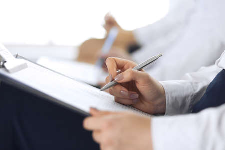 Business people taking part at conference or training at office, close-up. Women sitting on chairs and making notes like at queue or meeting Banque d'images