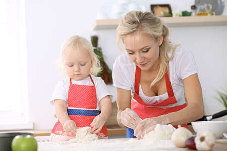 Little girl and her blonde mom in red aprons  playing and laughing while kneading the dough in kitchen. Homemade pastry for bread, pizza or bake cookies. Family fun and cooking concept