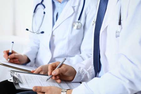 Deux médecins inconnus remplissant le formulaire médical sur le presse-papiers, juste les mains en gros plan. Les médecins posent des questions au patient ou discutent du programme de médication. Concept de soins de santé, d'assurance et de médecine Banque d'images