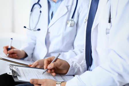 Two unknown doctors filling up medical form on clipboard, just hands closeup. Physicians asking question to patient or discussing medication program. Healthcare, insurance and medicine concept Foto de archivo