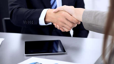 Business People shaking hands, finishing up a meeting in office, unknown human group Stock Photo