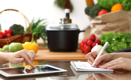 Close-up of human hands using tablet or touch pad. Two women in kitchen. Cooking, friendship or family fun concepts