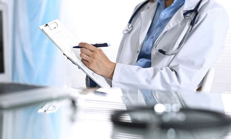 Female doctor filling up medical form on clipboard, closeup. Reflecting glass table is a physician working place. Healthcare, insurance and medicine concept Stockfoto