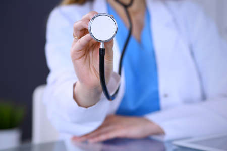 Doctor holds stethoscope head, close-up. Medical help and insurance in health care, best treatment and medicine concept. Blue tone of picture
