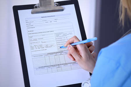 Female doctor filling up medical form on a clipboard, closeup. Healthcare, insurance and medicine concept