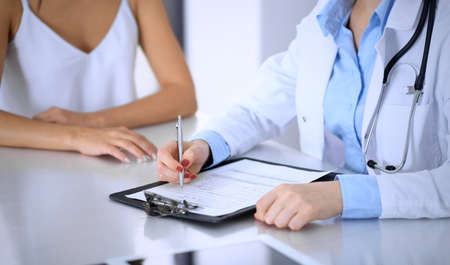 Doctor and  happy patient  talking while sitting at the desk, close-up of hands.  The physician or therapist filling up medical history records. Health care, medicine and patient service concept Stockfoto