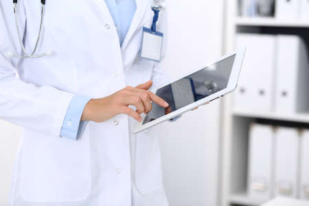 Doctor woman using tablet in clinic office. Unknown female physician at work while standing straight at hospital, close-up. Medicine and healthcare concept Stockfoto