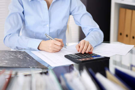 Unknown bookkeeper woman or financial inspector  making report, calculating or checking balance, close-up. Business portrait. Audit or tax concepts Stockfoto