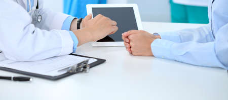 Doctor and patient discussing something, just hands at the table, white background. Physician pointing into tablet screen