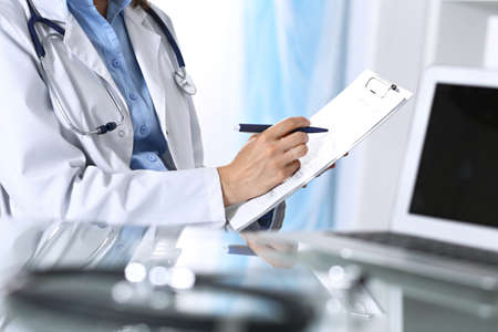 Female doctor filling up medical form on clipboard, closeup. Reflecting glass table is a physician working place. Healthcare, insurance and medicine concept. Stock Photo