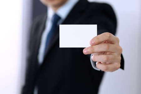 Unknown businessman hand holding business card with empty space, close-up.